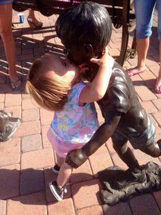 niña besando a una estatua