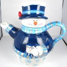 Navy Blue snowman teapot ... in dark blue jacket with striped scarf forming handle, red Christmas cardinal bird perched on tophat lid, snowflake decoration, white mitts, ceramic