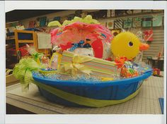The ultimate baby shower gift...a little pool filled with new baby items for a summer of fun! Lisa's Gift Wrappers