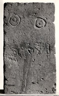 Rectangular limestone funerary stela with face inscribed with a name below a crudely carved pair of eyes near the top; surface very worn. Ancient South Arabian,  from Haram, Yemen.