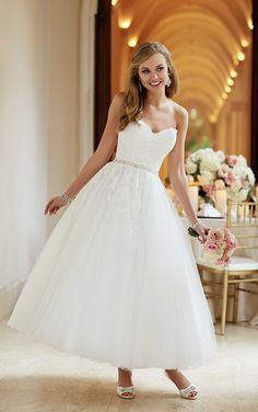 A blast from the past, this '50s-inspired wedding ball gown from Stella York features a fitted lace bodice, figure-flattering Diamante waist belt, and a whimsical tulle ankle-length skirt.