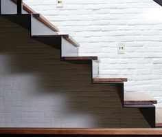 Made of steel, glass and walnut (by SKR Construction), the staircase's profile…