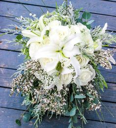 Sarah's bouquet was perfect for a winter wedding!  It was filled with white oriental lilies roses genestra eucalyptus and snowy white cedar.  #thefloralcottageflorist #louisianaweddings #batonrougewedding #batonrougebride #louisianabride #winterwedding #winterbride