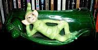 Light green pixie reclining on log.