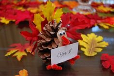 Pine Cone Turkey Place Card Holders - Fun Family Crafts.  Instead of leaves I like the idea of tracing handprints and using them as the feathers.