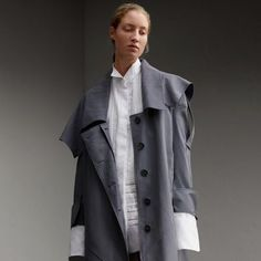 An English-made trench coat cut for a relaxed, asymmetric silhouette in lightweight tropical gabardine. The tonic-coloured cotton twill is woven for weatherproof protection at the Burberry mill, and is tumbled and washed to imbue softness and fluidity.