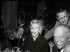 MARILYN MONROE together with director JOSHUA LOGAN in a portrait taken in 1955 while dining at The Ram restaurant in Sun Valley, Idaho during filming of Bus Stop (20th Century-Fox, 1956).