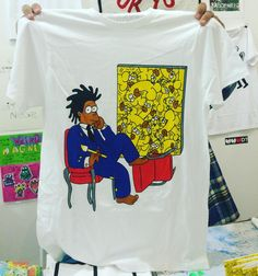 """""""The One with Basquiat"""" T-shirt Vacancy Projects (Los Angeles) table X04 #NYABF This LA publisher's table is filled with art historical parodies from a rug in the shape of a Campbell's soup can branded with the perennial Seinfeld saying """"No Soup for You"""" to a Robert Raushenberg poster emblazoned with the distinctive double-R logo of the 1990s rap supergroup Ruff Ryders. This T-shirt features a Simpsons-themed parody of Jean-Michel Basquiat's famous 1985 New York Times Magazine cover. (…"""