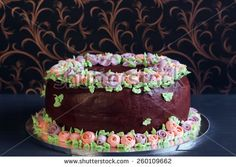 Homemade chocolate cake with colorful cream flowers on dark background