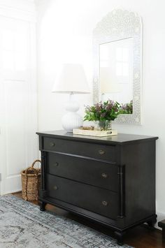 Chic foyer boasting a bone inlay mirror over a black dresser atop a black and blue rug.