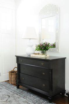 Chic foyer boasting a bone inlay mirror over a black dresser atop a black and blue rug.