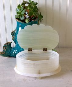 This is a beautiful heavy stone ( onyx) trinket / jewelry box! Has a clam shell / seashell design with hinged top & ball feet. Complete stone box except for metal hinges & pins in feet. In very good vintage condition, ready for keepsakes or fine jewelry. Great for coastal or beach wedding decor! Measures 7 long X 5 wide, a little over 2.75 height  Thanks for shopping YellowHouseDecor!  Please visit my sisters shop for more vintage items ( ellansrelics02)  🌴Shipping cost reflects weight of…