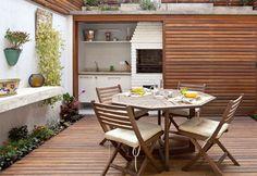 Área gourmet com deck de madeira e porta de correr
