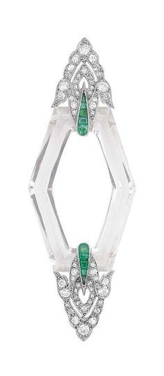 Art Deco Platinum, Rock Crystal, Diamond and Emerald Brooch The modified hexagonal-shaped rock crystal plaque tipped by pierced fancy-shaped platinum terminals, accented by old-mine and single-cut diamonds and calibre-cut emeralds, with French assay mark, circa 1920.