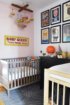 Contemporary nursery - chrome baby bed, mobile of hanging vintage tops, bight contemporary art with white mats and black frames, gray area run with white line design, would work well for boy or girl and could adapt as baby gets older
