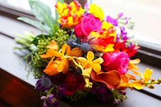 Brightly colored bridal bouquet mixed roses, calas, orchids and more.