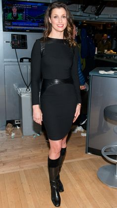 BRIDGET MOYNAHAN wears a leather-trim black dress and knee-high black boots to ring the New York Stock Exchange closing bell in N.Y.C.