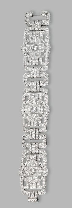 PLATINUM AND DIAMOND BRACELET, CIRCA 1930.  Composed of openwork rectangular plaques set with 3 larger old European-cut diamonds weighing approximately 2.00 carats, further set with smaller old European-cut, old mine, single-cut and baguette diamonds weighing approximately 19.75 carats, length 7 3/8  inches.