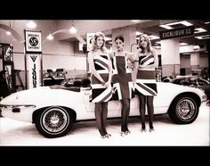 These ladies celebrate the Jaguar E-Type V12 Roadster with these Union Jack dresses...years before Ginger Spice brought them to style.