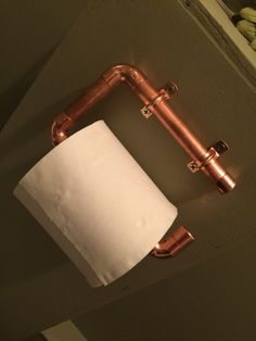 Copper pipe loo roll holder.