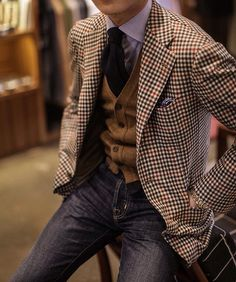 Brown and red guncheck windowpane blazer, brown cardigan, blue shirt, navy tie, jeans