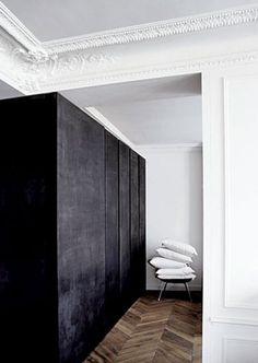 Black wardrobe, chevron flooring.