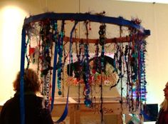 Reggio Emilia: Hanging Art -  A large embroidery hoop with all kinds of string, yarn and ribbon hanging from it.