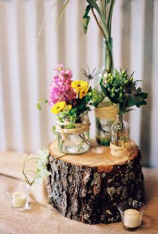 For a rustic or enchanted forest themed wedding - wildflowers tucked into glass jars wrapped in twine, all arranged atop a rustic tree stump base