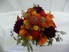 red pin cushion protea, craspedia balls, scabiosa pods, celosia, dark purple dahlia, orange calla lilies,and seeded euc.