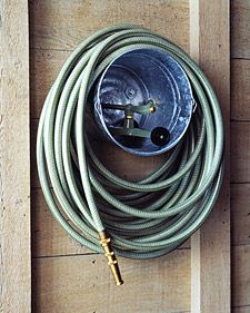Use a galvanized paint bucket to make a practical and inexpensive caddy for a garden hose and sprinkler. | @Martha Stewart Living marthastewart.com
