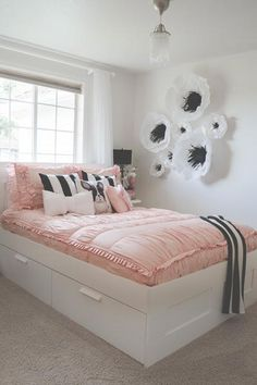Everything in this gorgeous bedroom goes together perfectly, from the black and white paper flowers on the walls to the pink bed with striped decorative pillows.