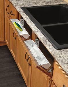 Utilize those fake drawers under your sink by adding trays that store your sponges.