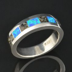 Gray dinosaur bone and blue green laboratory grown opal sterling silver ring handmade by Hileman Silver Jewelry.  Makes a unique men's wedding ring! #dinosaurbonerings #uniqueweddingrings #dinosaurbone