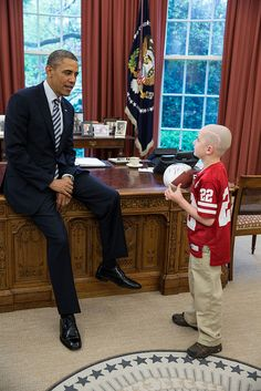 President Barack Obama greets Jack Hoffman, 7, of Atkinson, Neb., in the Oval Office, April 29, 2013. Hoffman, who is battling pediatric brain cancer, gained national attention after he ran for a 69-yard touchdown during a Nebraska Cornhuskers spring football game. Hoffman holds a football that the President signed for him.