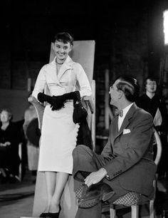 So that's how they kept their costumes pristine! In this behind-the-scenes photo from The Lavender Hill Mob, a young Audrey Hepburn can be seen relaxing onto a slightly reclined board with armrests—a standing chair 1951