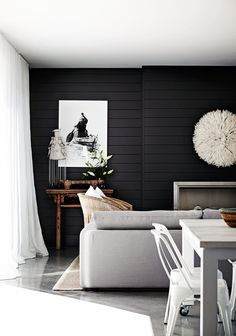 "The dark feature wall – painted in Porter's Paints ""Van Helsing"" – helps define the living area and provides a stunning contrast to the light palette. ""It creates a different area to enjoy in the house,"" Eduardo says."