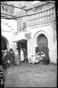 Marrakech Dans les souks, marocains devant une échoppe et une porte d'entrée 1924
