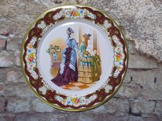 "Daher Decorated Ware Victorian Ladies metal collector plate. Shows two Victorian Ladies talking, with a little boy at the door. Decorative gilded floral border. Measures 8"" across. (20.32cm). Auctiva Free Image Hosting. 