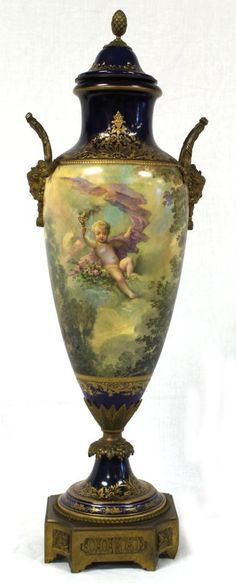 """Sevres French porcelain urn with lid, rich cobalt matte and glossy ground with extensive raised gilt highlights, body reserved with continuous landscape and 18th century heavenly figures, gilt bronze-mounted mask handles, raised on bronze base, signed by artist """"Schill""""."""