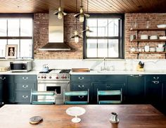 dark (peacock blue) lower cabinets, industrial / loft style brick walls, open wood shelving, white countertop kitchen, dark wood plank (shiplap) ceiling