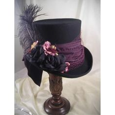 This Mad Hatter Hat features Blackfelt tall Mad Hatter with Plumsatin scarf, plumtulle, black & Plum flowers and black ostrich feather.