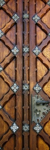 detail of handle and joining of ornate wooden door embossed with metal ornaments