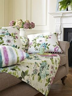 Prestigious Textiles -  Italian Garden Fabric Collection - Pastel coloured floral throw and cushions with pink bead fringing, with a striped cushion, on a brown fabric sofa, with a white vase