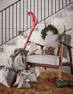 Stoffgeschenktüten aus AINA Meterware in Grau in verschiedenen Größen stehen neben einem Sessel.