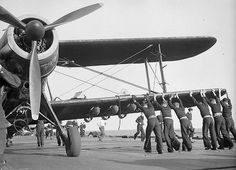 A Fairey Albacore of 820 Squadron, Fleet Air Arm with full bomb-racks, being wheeled into position by several sailors lined along the wing of the aircraft on the flight deck of HMS FORMIDABLE during the North African landings. Aircraft Photos, Ww2 Aircraft, Military Aircraft, Royal Navy Aircraft Carriers, Old Planes, War Thunder, Flight Deck, Royal Air Force, Second World