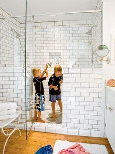 large shower with two half walls framing door, white subway tile, wood floor in bath, bathroom Double Shower Heads, Shower With Half Wall, Subway Tile Showers, Subway Tiles, Shower Tiles, Walk In Shower, Big Shower, Modern Shower, Shower Door