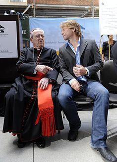 Jon Bon Jovi chats wiith Cardinal Justin Rigali at a Wednesday news conference in Philadelphia for the homeless advocacy groups Project HOME and Bethesda Project.  The non-profits are forming a joint venture to build an environmentally friendly housing facility for 79 men and women called St. John the Evangelist House.