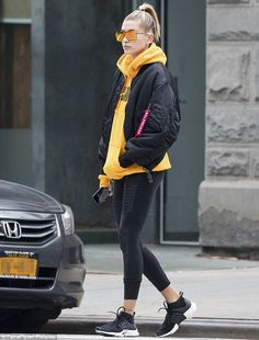 She s a beauty  The 19-year-old bundled up in the tangerine toned hoodie  with black leggings and a matching hued bomber jacket d679bdca08