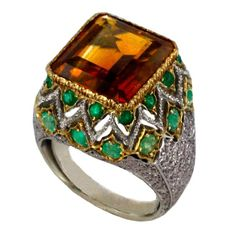 A stunning example of complex Buccellati craftsmanship, this ring showcases a dramatic square-cut citrine surrounded by round emeralds set into delicate white-gold fretwork.