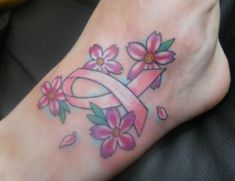 Ankle tattoo with pink ribbon in the middle of Flowers
